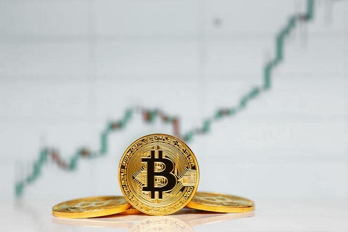 Picture of Bitcoin token against stock graph to accompany post about the SEC saying that Bitcoin is not a security